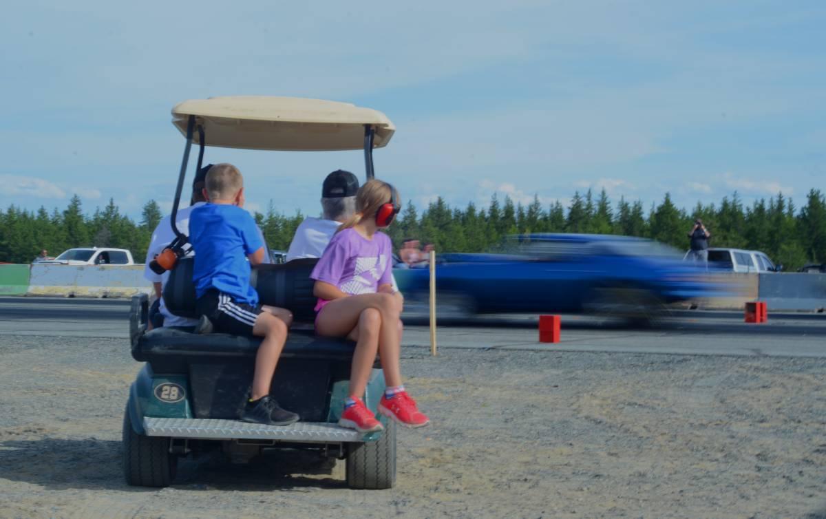 children sit in a golf cart wearing earmuffs