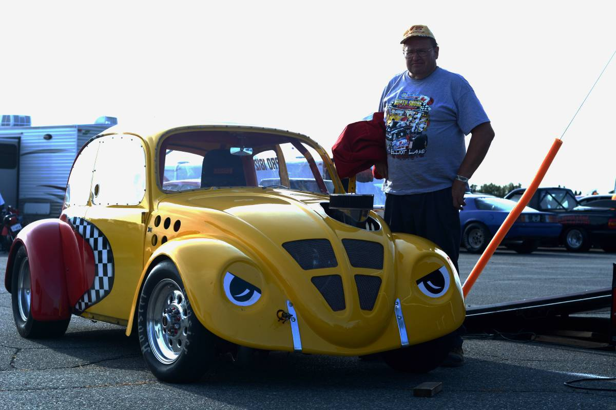 man stands with yellow Volkswagon Beetle