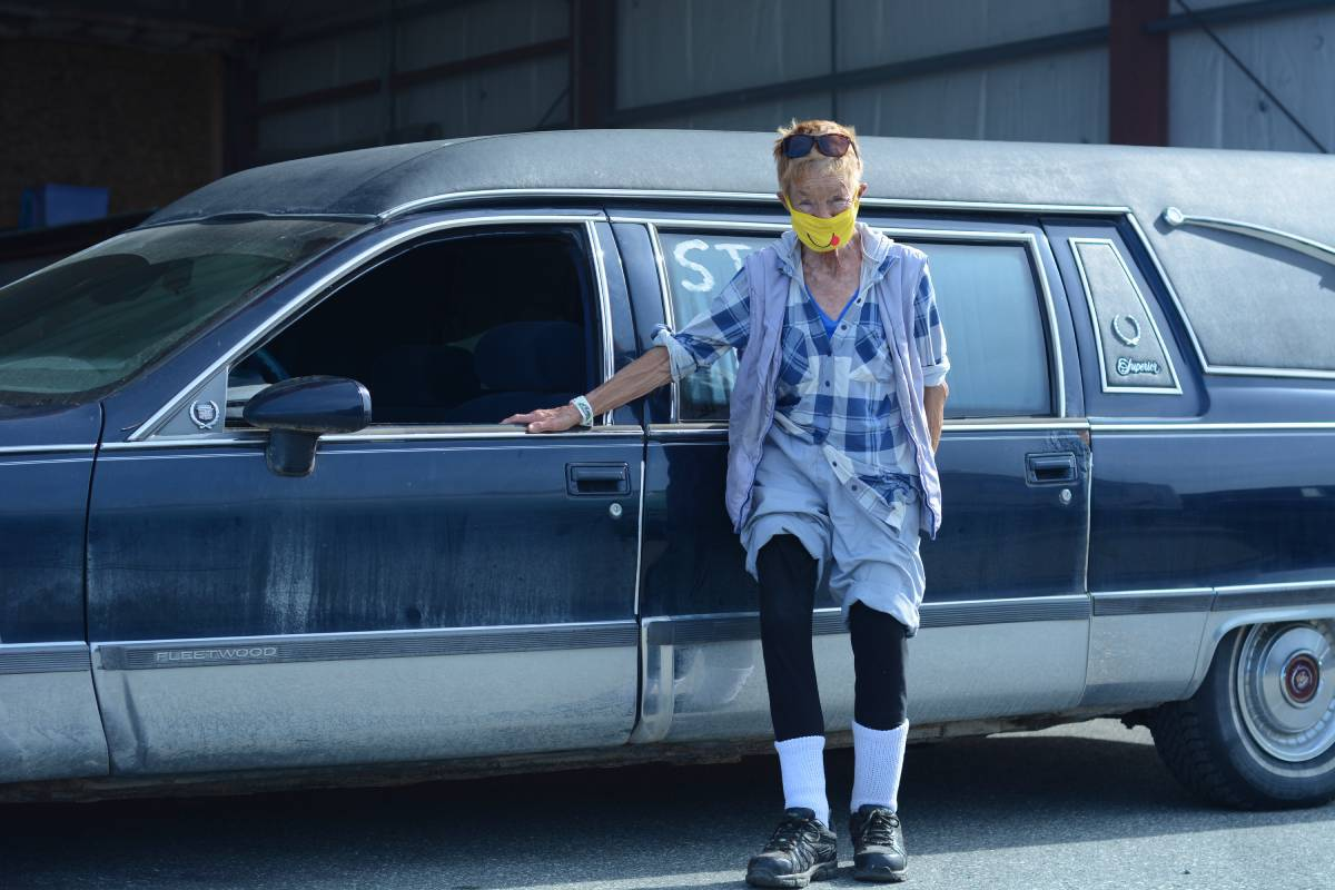 a woman leans against a hearse