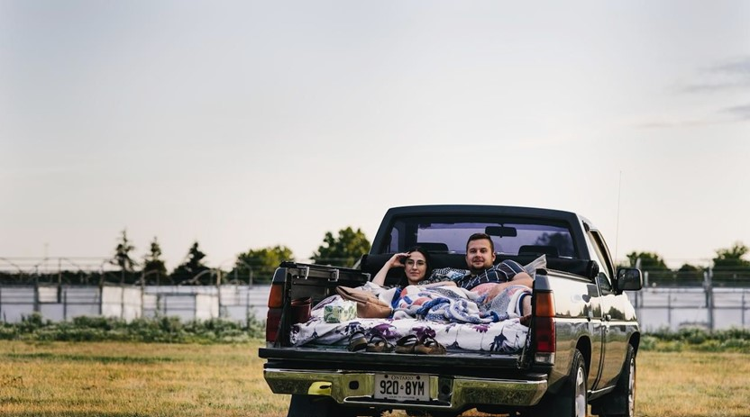 Two people sitting in the back of a pick-up truck