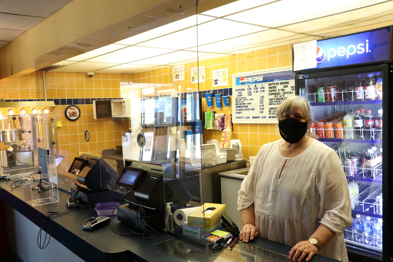 masked woman stands behind a concession stand