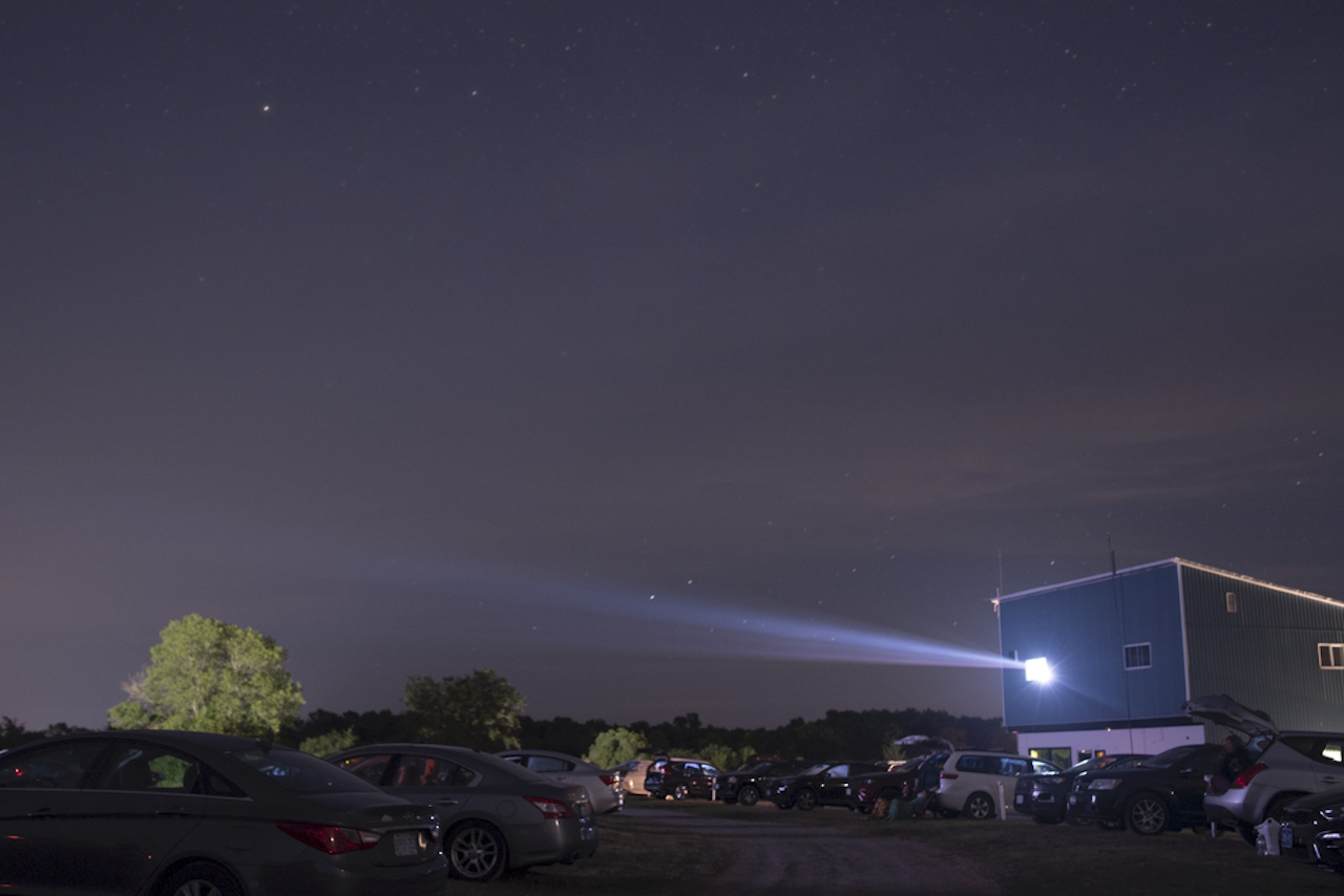 a projector showing a movie at a drive-in