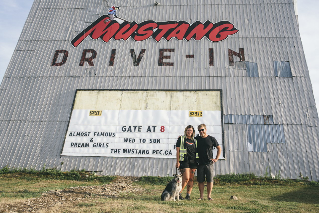 a couple stands in front of a drive-in sign