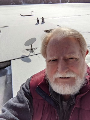man with a white beard stands in front of a satellite dish