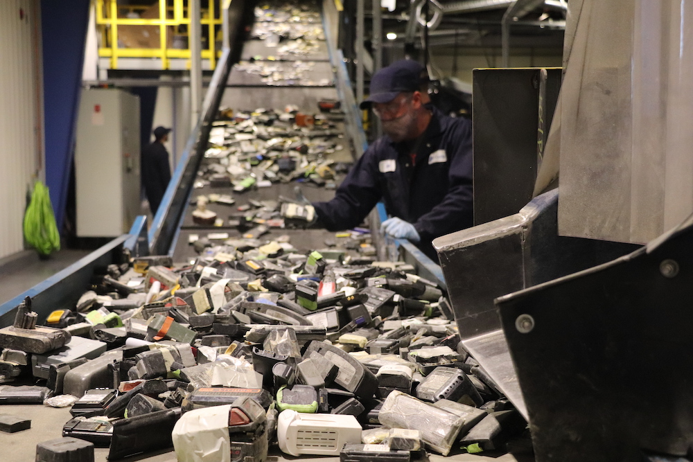 worker bends over conveyor belt full of used electronics