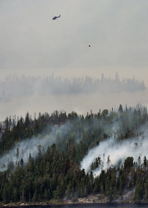 plane flying high above a forest fire