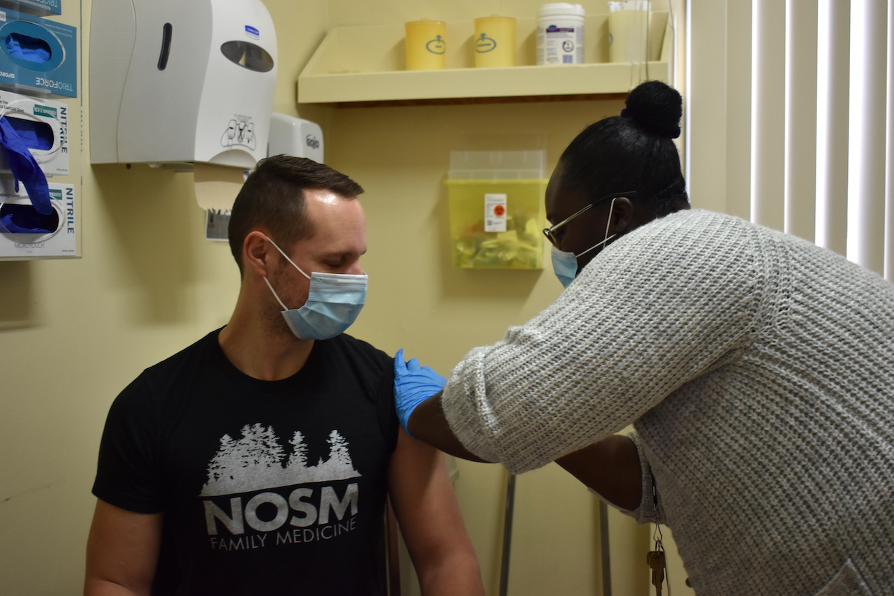 a man in a black T-shirt is vaccinated by a woman in scrubs
