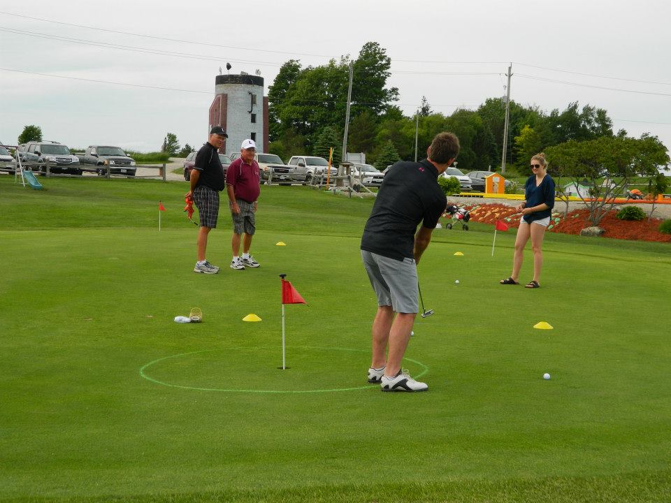 people playing golf in front of a large golf-bag sculpture