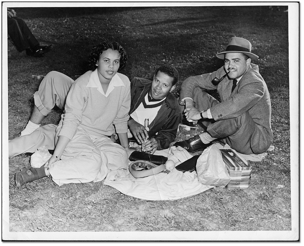 two men and a woman sitting on a blanket