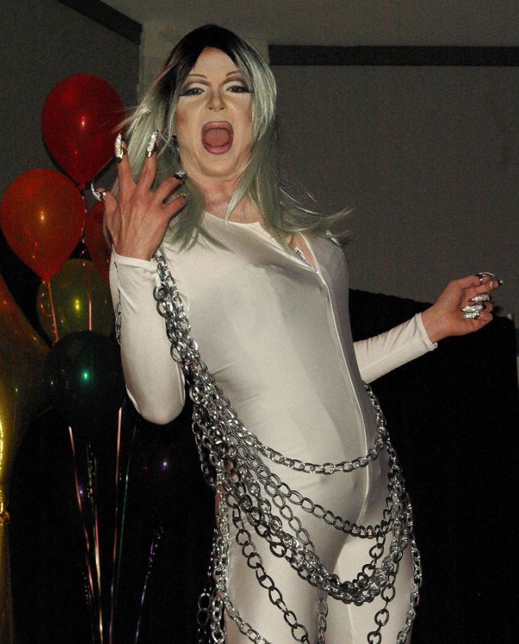 Person in outfit and makeup performs on a stage.