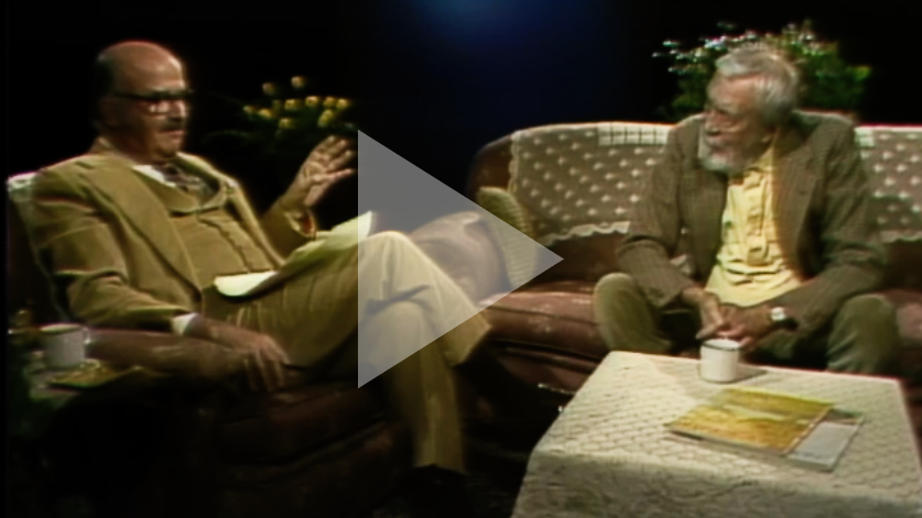 Elwy Yost interviews film director John Huston. A play symbol is superimposed over the image