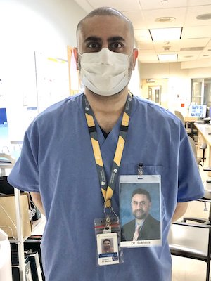 a man in scrubs and a face mask