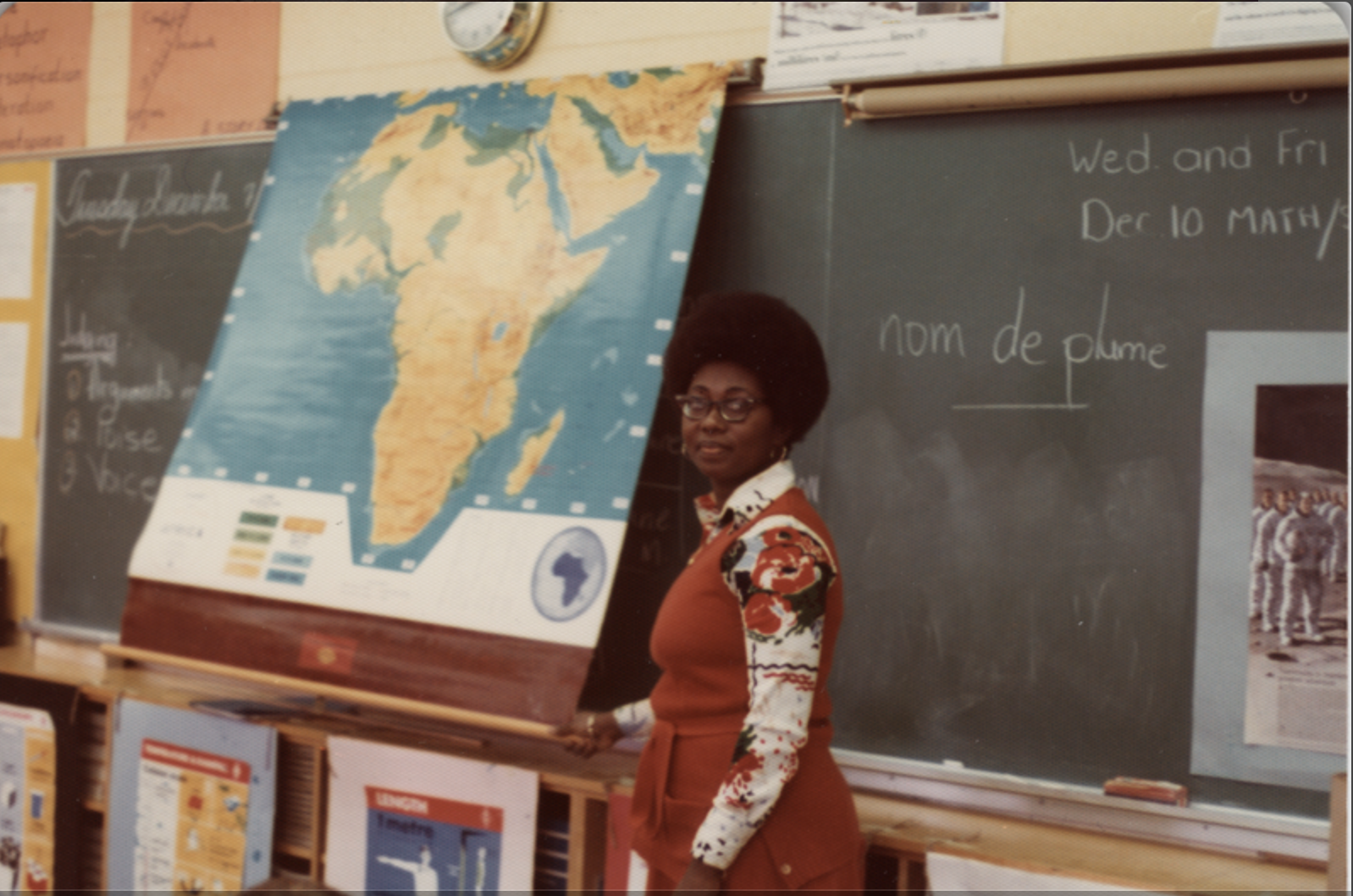 a woman stands in front of a blackboard