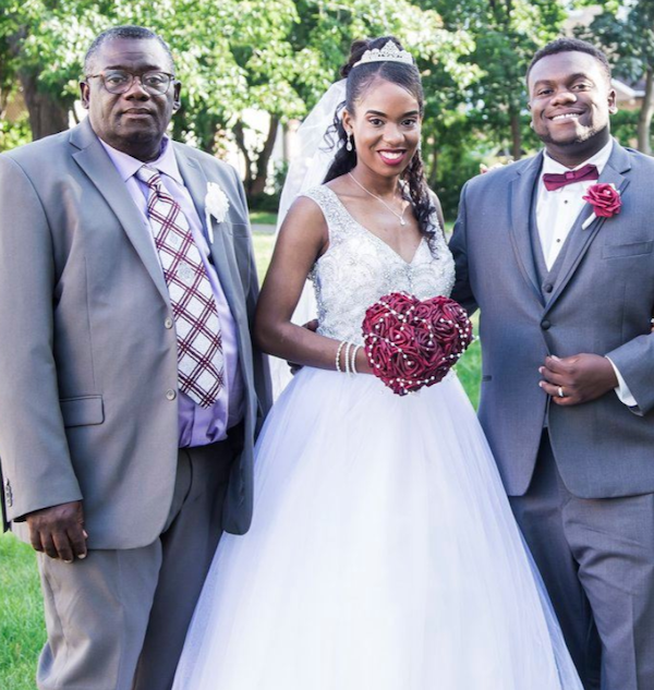 a man stands with a bride and groom