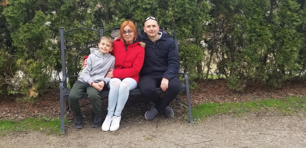 woman, man, and young boy sitting on a bench