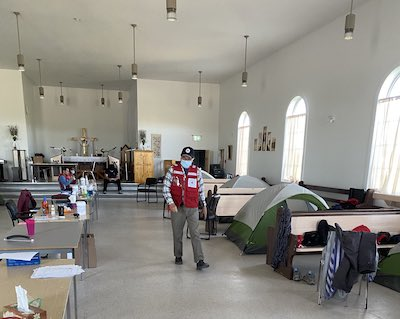 man walks through church filled with tents