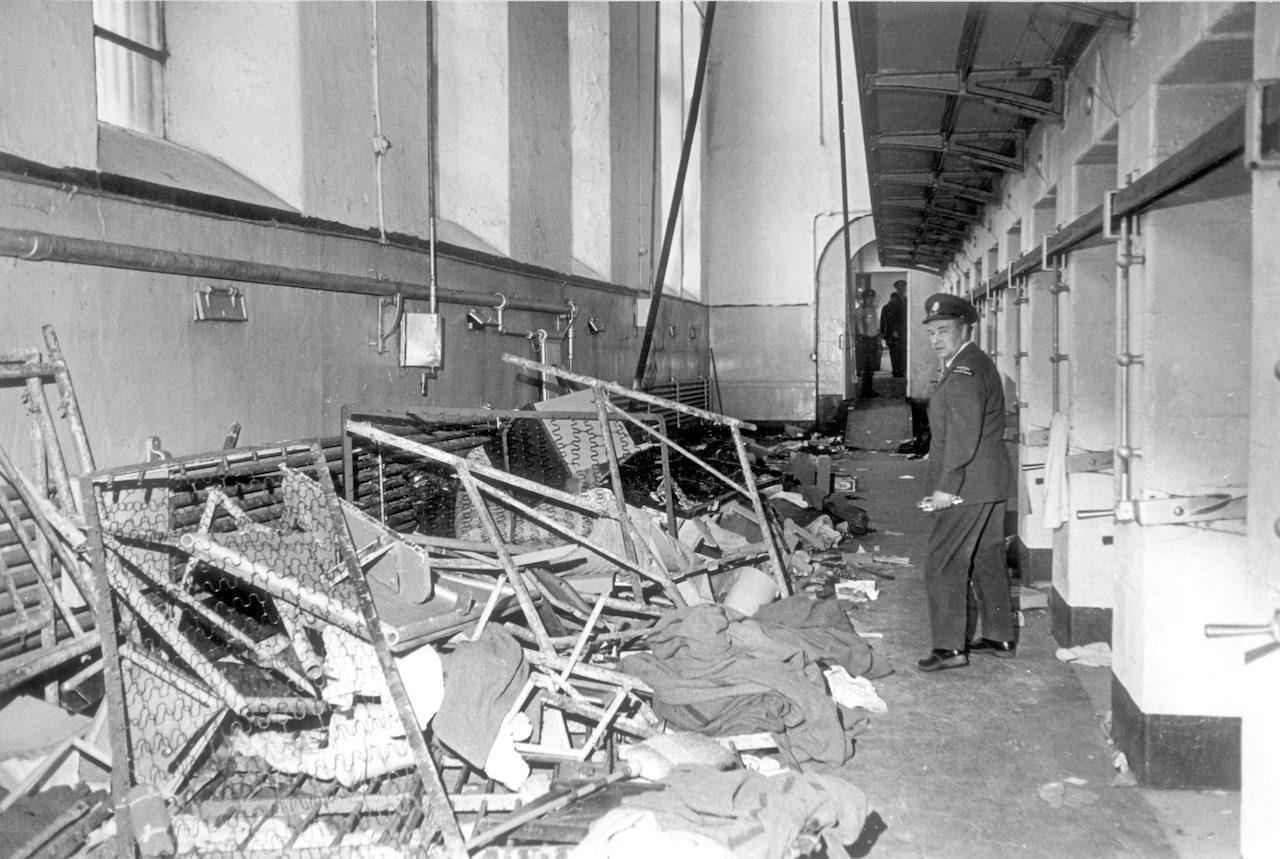 a man in uniform surveys a scene of destruction