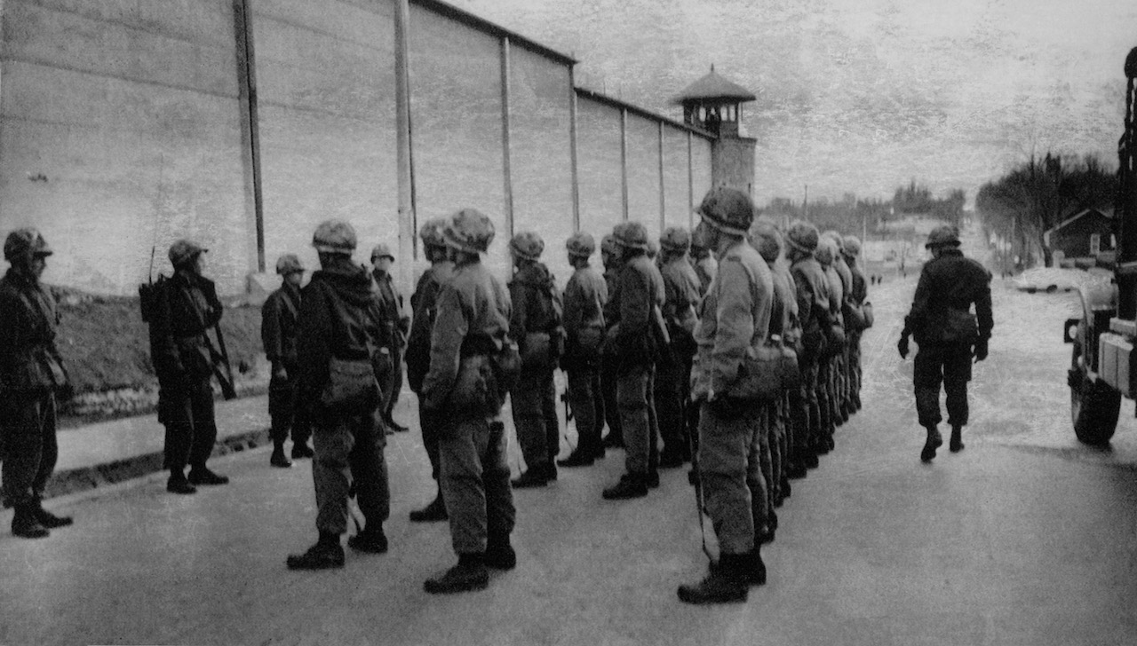 soldiers lining up outside a fence