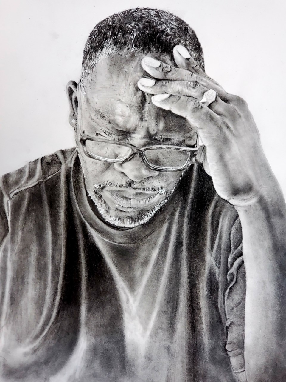 a man in glasses rests his head on his hand
