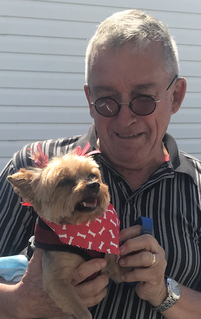 man in glasses holding a small dog