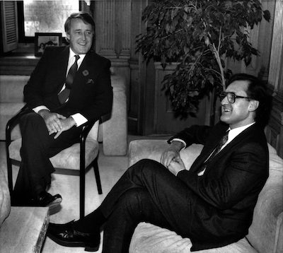 black and white photo of two suited, seated men talking