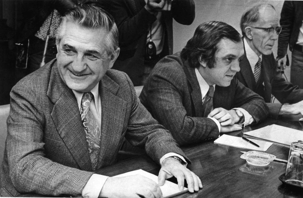 three seated men in suits