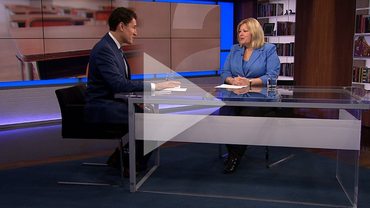 Steve Paikin interviews Lisa Thompson. A play symbol is superimposed over the image