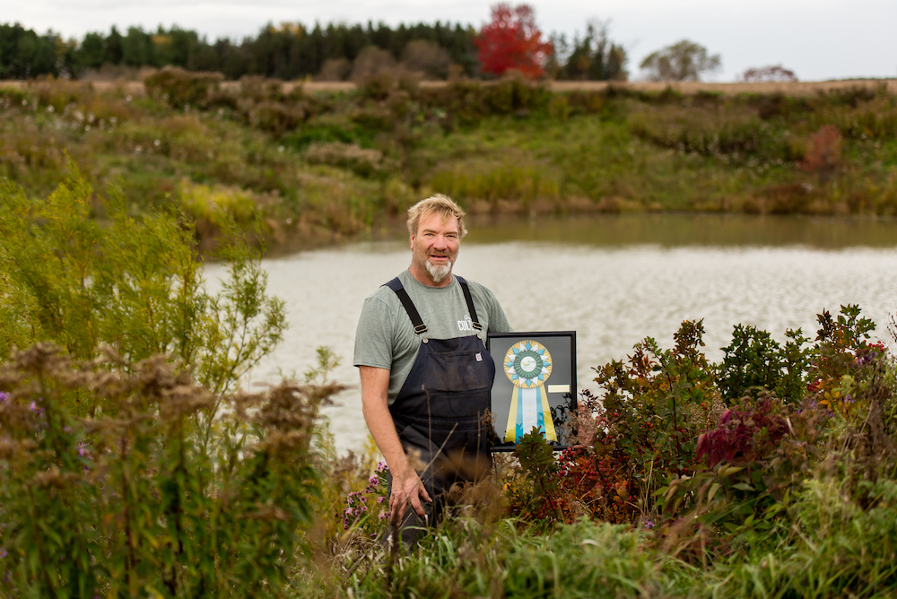 man standing in front of a pond holding a framed award
