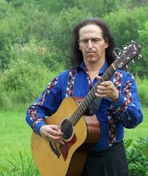 man in blue shirt playing a guitar