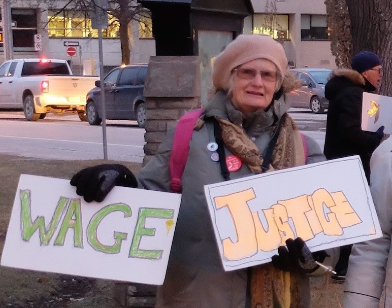 """woman holds two signs reading """"wage"""" and """"justice"""""""