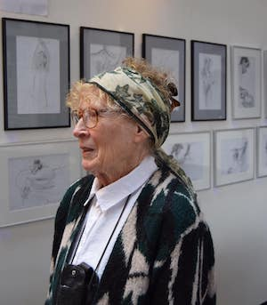 woman in headscarf standing in front of rows of art