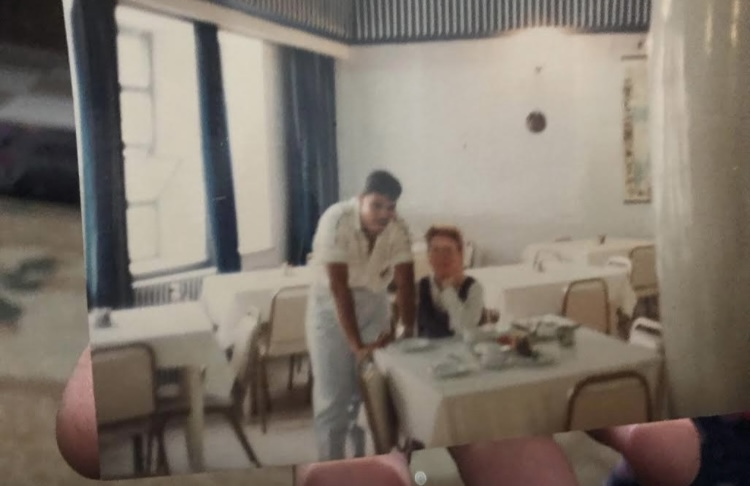 photo of a standing man and seated woman in a restaurant