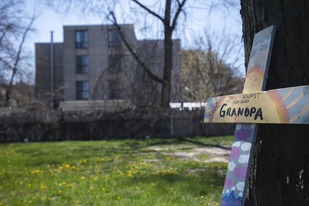 "a cross reading ""grandpa"" leans against a tree"
