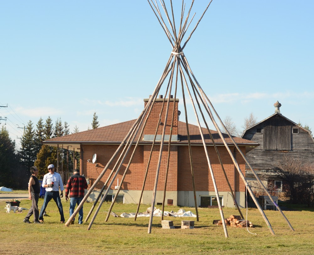 men standing by tipi poles