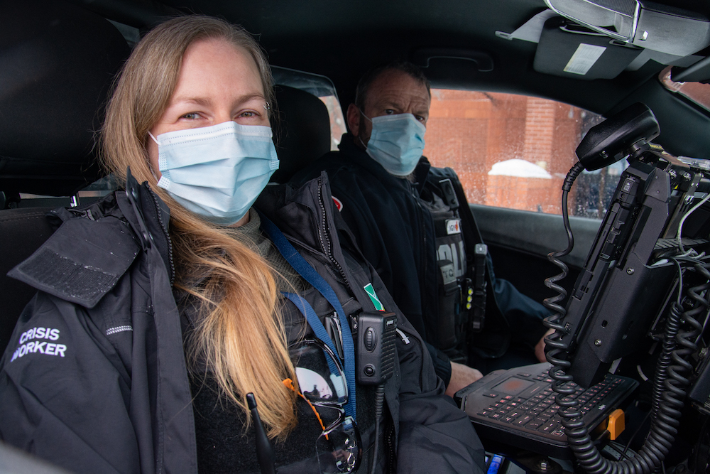 a masked woman and man in a car
