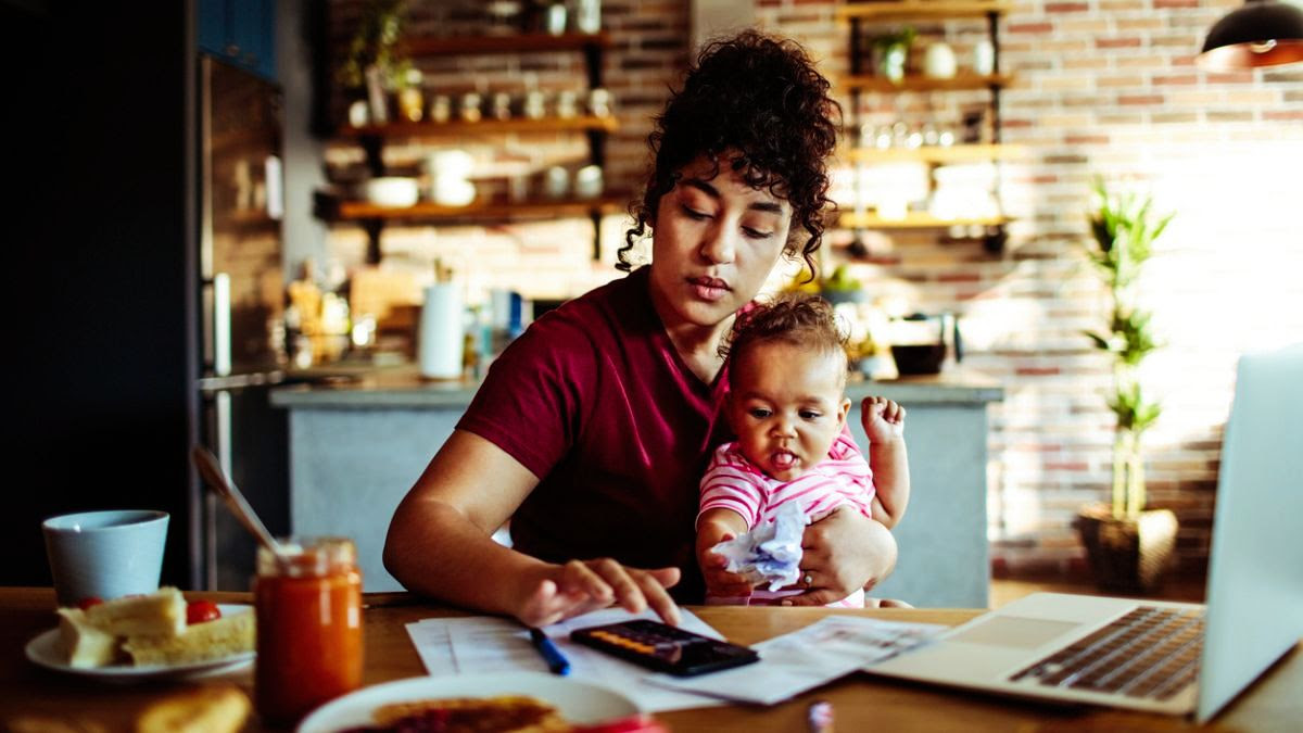 Mother holding baby and using a calculator