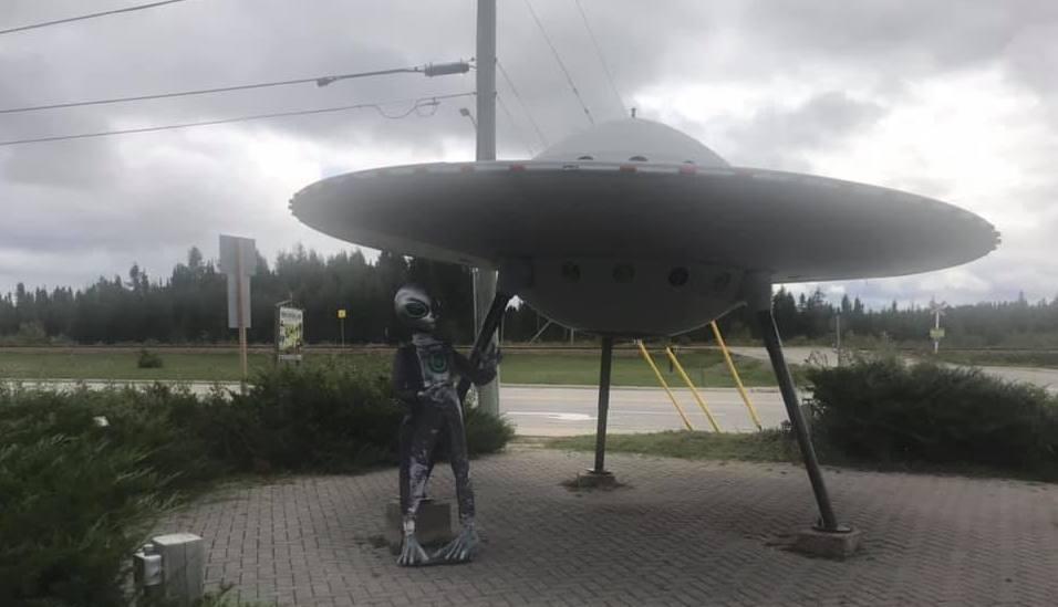 an alien figure stands beside a model flying saucer
