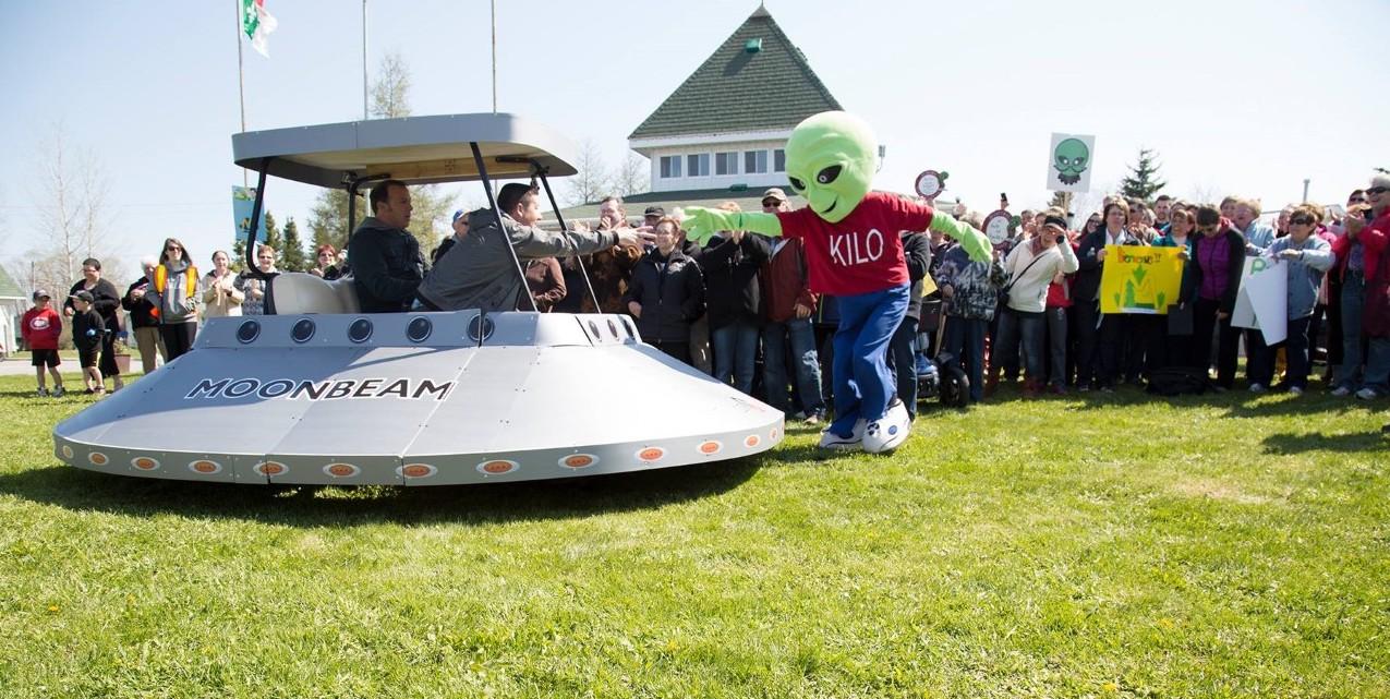 a green alien mascot pursues a flying saucer