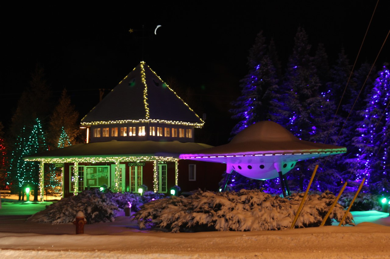 nighttime shot of a building and flying-saucer model decorated with lights