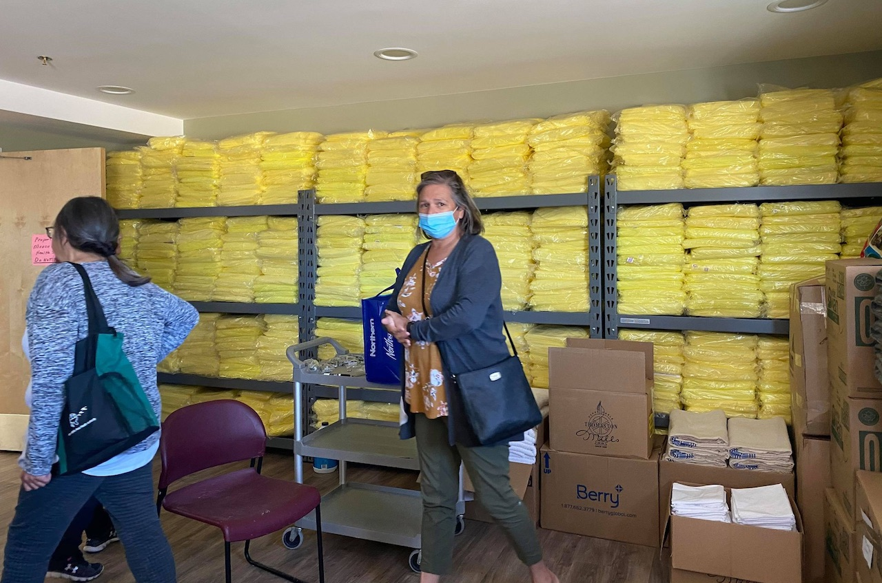 A woman wearing a mask stands in front of supplies