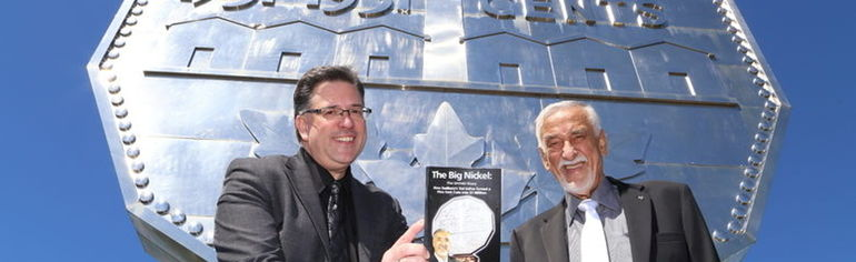 two smiling men holding a book in front of a giant nickel