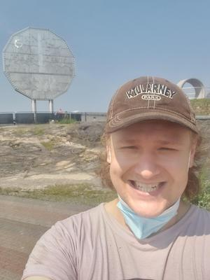 a smiling man in front of a giant nickel