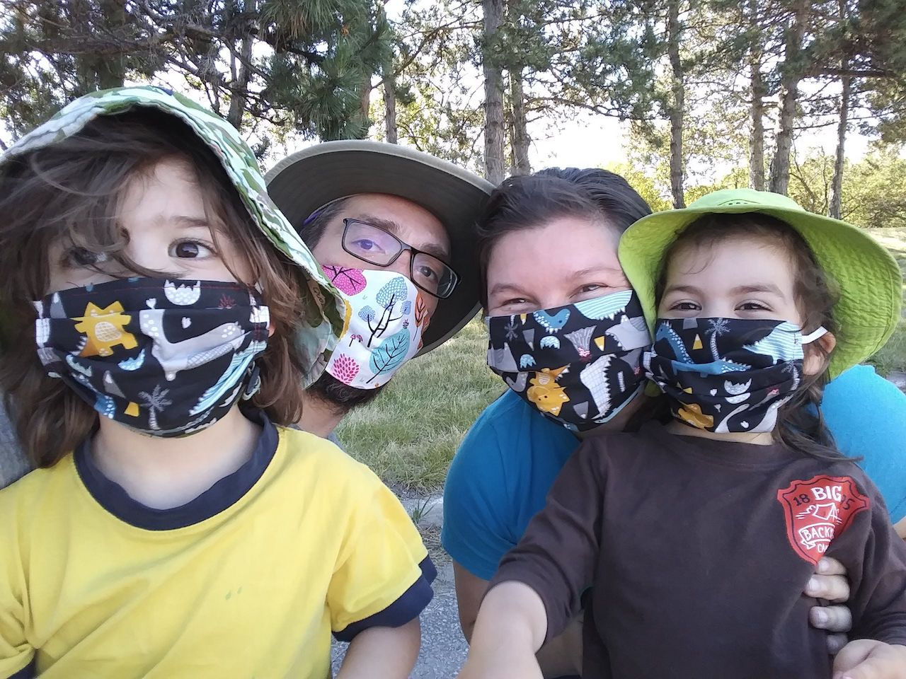 a man, a woman, and two children wearing masks