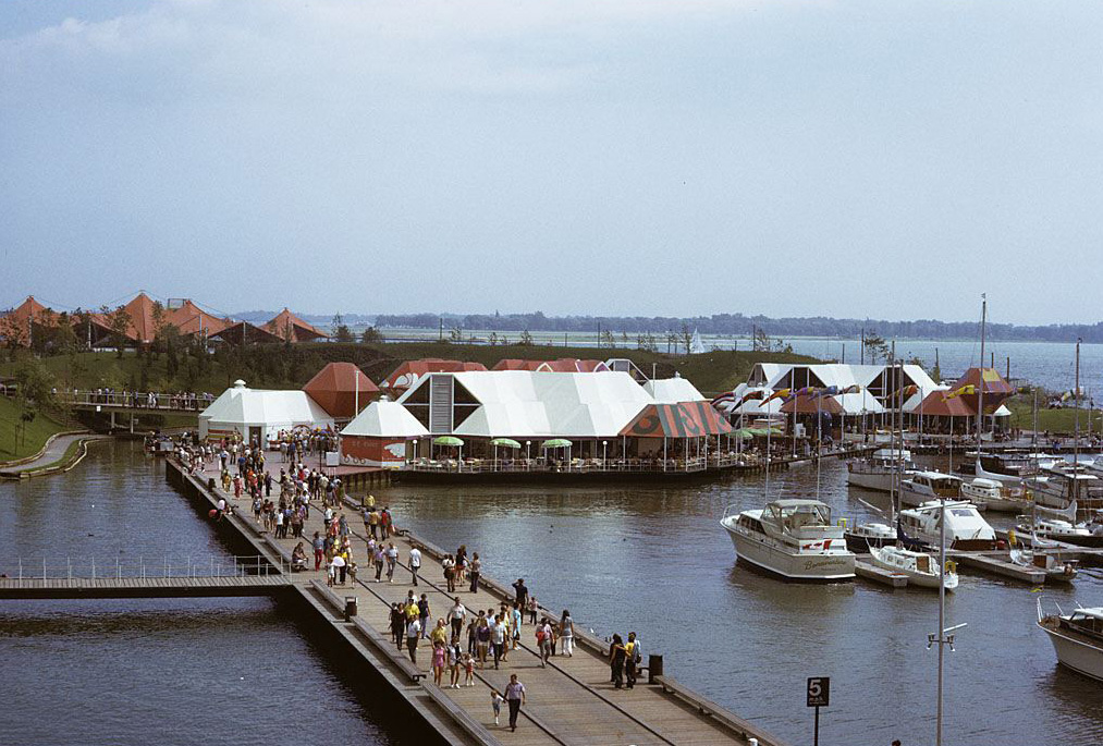 a building with a walkway — filled with people — by the water