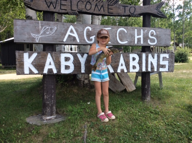 a girl holds a fish in front of a wooden sign