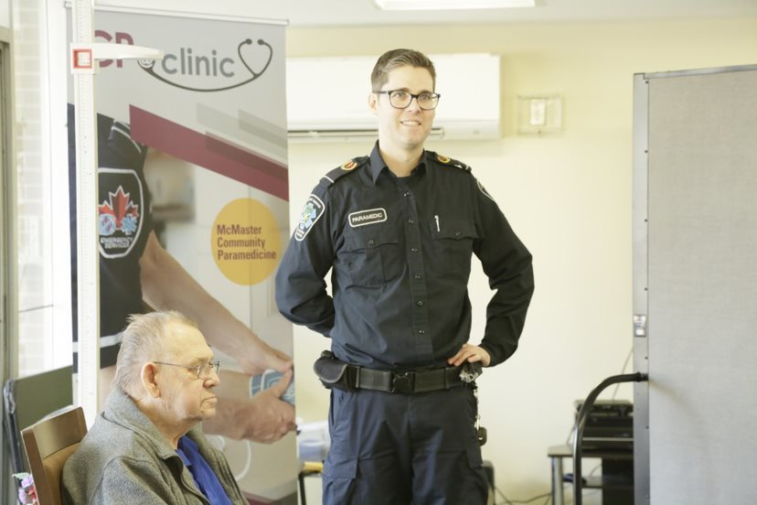 a smiling paramedic stands beside a seated elderly man