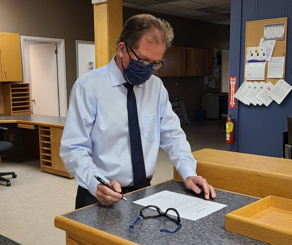 a masked man stands at a desk and signs a paper