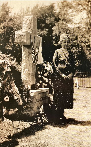 a woman stands beside a grave