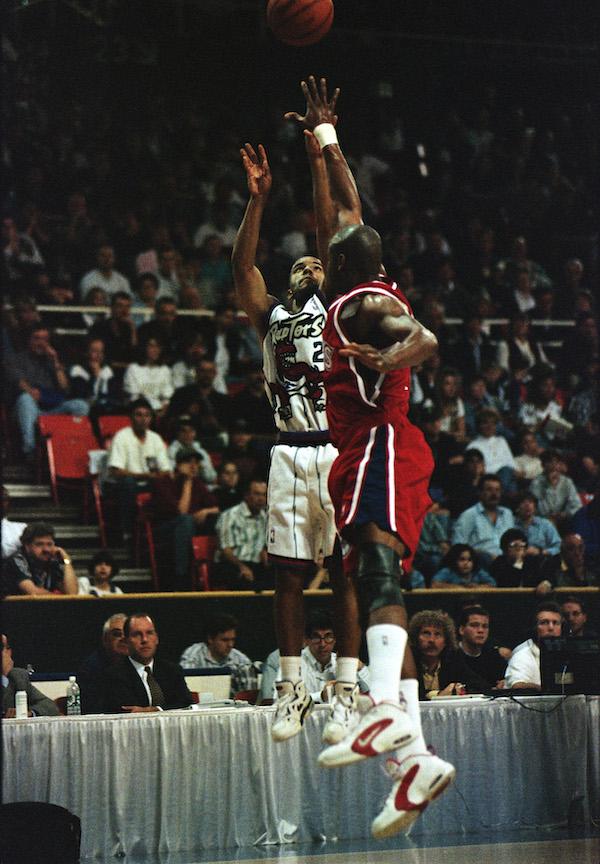two men jump at a basketball hoop
