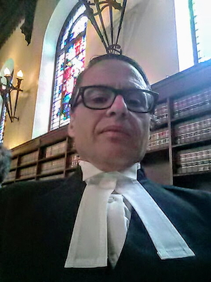 man with glasses in legal robes